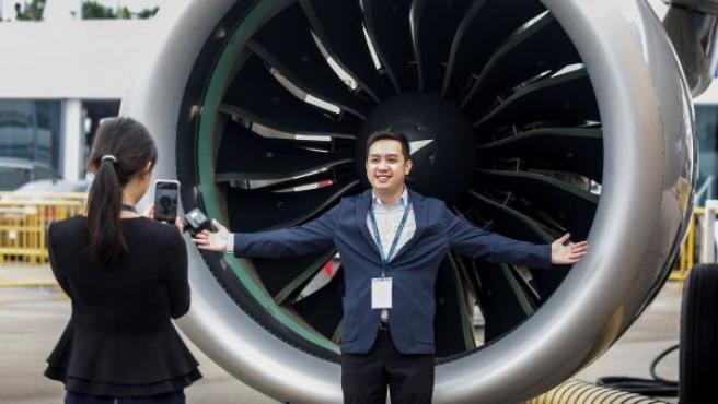 Un hombre posa junto a la turbina de un avión expuesto en el Salón Aeroespacial de Singapur.