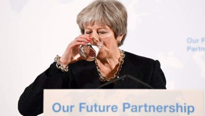 La primera ministra de Reino Unido, Theresa May, bebiendo agua.