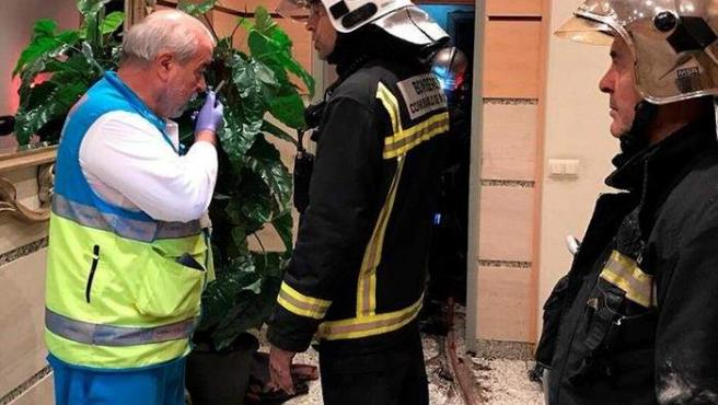 Un miembro del SUMMA y varios bomberos, en la puerta de la vivienda en la que dos menores fueron encontrados muertos tras un incendio ocurrido en la calle Benjamín Palencia, en Getafe.