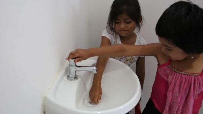 Dos niñas juegan en los baños del colegio de la comunidad Huaytu de Buena Vista, en el departamento de Santa Cruz, Bolivia.