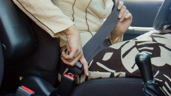 Una mujer se coloca el cinturón de seguridad en un coche.