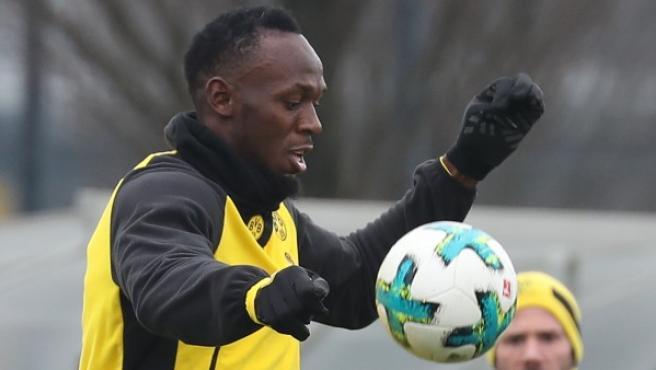 El exatleta jamaicano Usain Bolt (izq), plusmarquista mundial de 100 y 200 metros, participa en un entrenamiento del Borussia Dortmund.