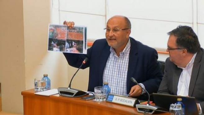 El socialista Abel Losada muestra fotografías durante el debate sobre la mina