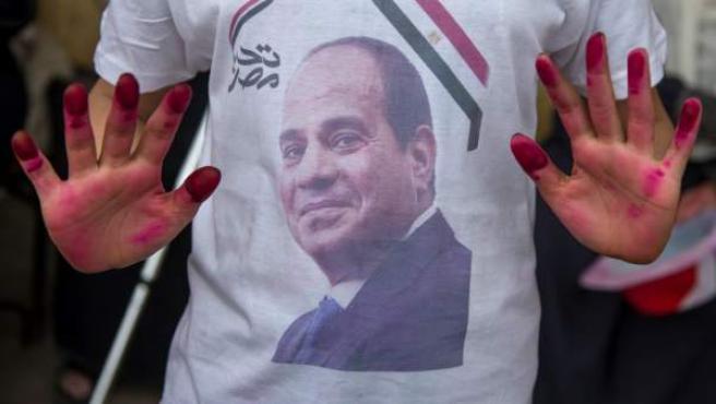 Una persona muestra una camiseta con el rostro del presidente egipcio, Abdelfatah al Sisi.