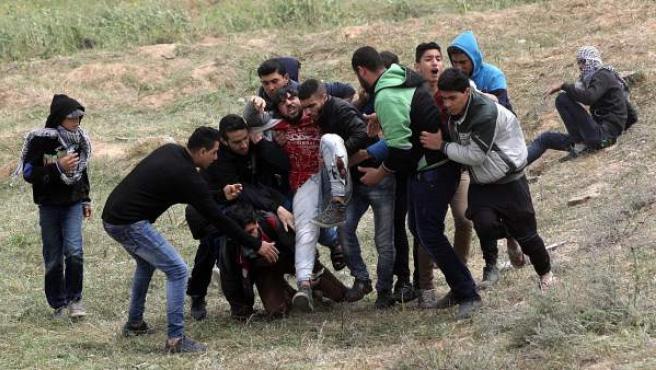 Varios palestinos ayudan a un compañero herido durante los enfrentamientos con soldados israelíes en el este de Beit Hanun.