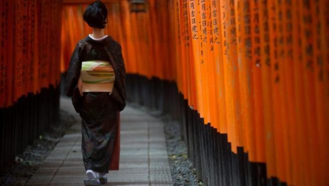 Una mujer, vestida con un kimono, pasea bajo una serie de arcos torii sintoístas, en el templo Fushimi Inari de Kioto (Japón).