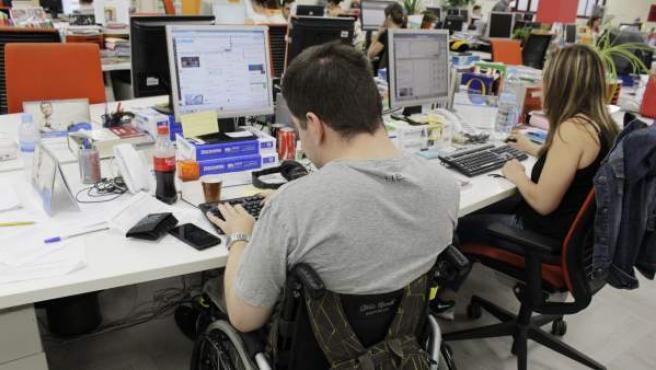 Una personas con discapacidad frente a un ordenador.