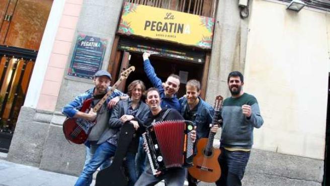 Los integrantes del grupo catalán La Pegatina posan junto al que fue su bar durante tres días en Madrid