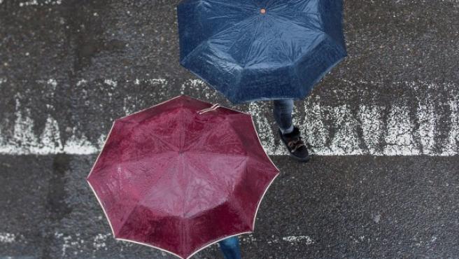 Dos personas cruzan un paso de peatones portando paraguas.