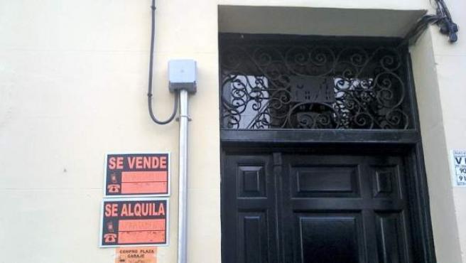 En la fachada de una casa, el cartel de un apartamento que se vende o alquila.