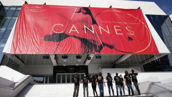 Trabajadores colocan el póster oficial del Festival de Cine de Cannes 2017, en el Palacio de los Festivales de la ciudad francesa.