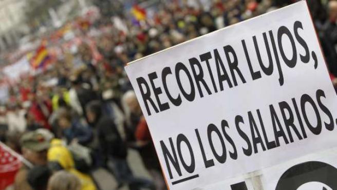 """Una pancarta en la que puede leerse """"Recortar lujos, no los salarios"""", durante la manifestación con motivo del Primero de Mayo."""