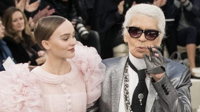 El diseñador alemán Karl Lagerfeld (dcha) sale a la pasarela lanzando un beso, acompañado por la modelo francoestadounidense Lily-Rose Depp, tras presentar su colección de alta costura primavera-verano 2017 para Chanel, durante la Semana de la Moda de París (Francia).
