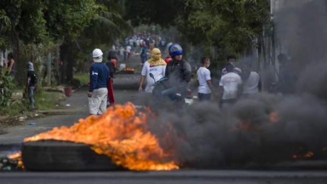 Vista de una llanta incendiada por manifestantes durante el cuarto día de protestas en Managua (Nicaragua).