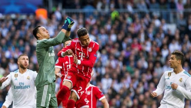El portero costarricense del Real Madrid Kaylor Navas (2i) intenta despejar ante el centrocampista francés del Bayern de Munich Corentin Tolisso (2d) .