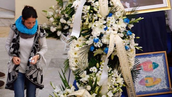 Patricia Ramírez, la madre de Gabriel Cruz, pasa junto a varias coronas de flores colocadas en la capilla ardiente por su hijo.