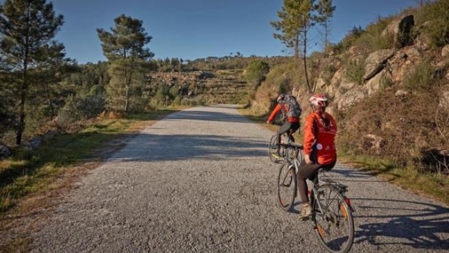 Dos turistas recorren en bicicleta una ruta por al Sierra del Caramulo.