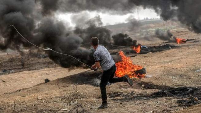 Un joven palestino lanza una piedra con su honda contra miembros del Ejército israelí, durante unos enfrentamientos en Gaza, Palestina.