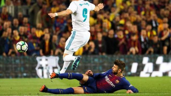 Piqué, lanzándose al suelo para robar la pelota a Benzema.