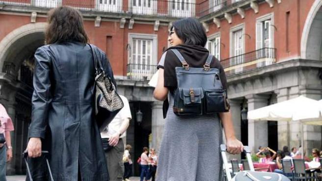 Dos turistas recorren la Plaza Mayor con sus maletas.