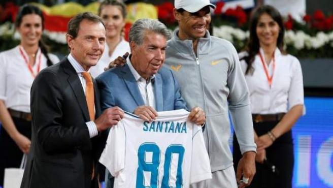 El extenista Manolo Santana, con el exfutbolista Emilio Butragueño y el tenista Rafael Nadal, tras recibir una camiseta del Real Madrid por su 80 cumpleaños.