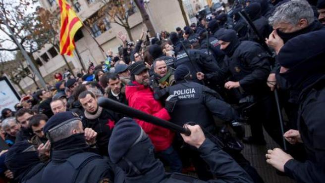 Un agente de los Mossos levanta una porra ante uno de los manifestantes contrarios al traslado de las obras del Museo de Lleida a Sijena.