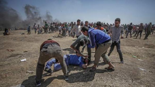 Manifestantes palestinos ayudan a un herido cerca de la frontera con Israel.