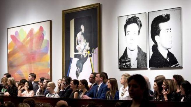 """Las piezas """"Devolving"""" del artista Morris Louis (i), """"Study of a Portrait"""" de Francis Bacon (c) y """"Most Wanted Men No. 11, John Joseph H., Jr."""" de Andy Warhol son presentadas durante una subasta de Arte Contemporáneo y Postguerra de la casa de subastas Christies, en Nueva York (Estados Unidos)."""