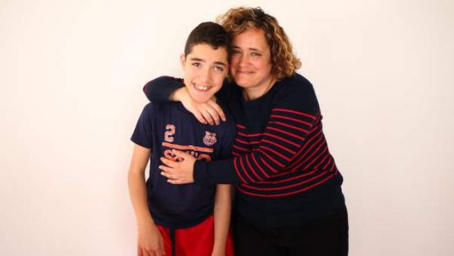Asier, de 12 años, que fue diagnosticado de parálisis cerebral a los dos meses de nacer, posa junto a su madre, Mayte.