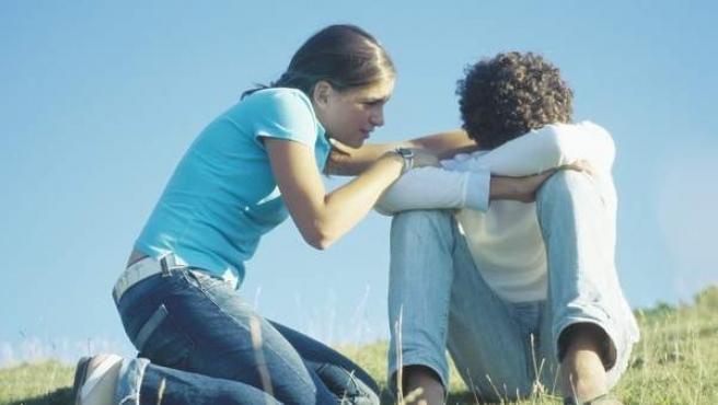 Dos jóvenes, en actitud de pena y consuelo.