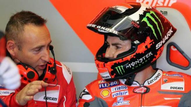 Jorge Lorenzo conversa con un mecánico en el box de Ducati.