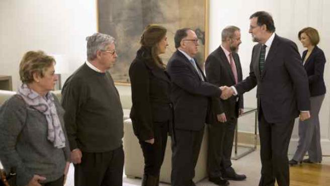Mariano Rajoy, acompañado por la ministra de Defensa, Maria Dolores de Cospedal, saludando a los representantes de la Asociación de Víctimas del Yak-42.