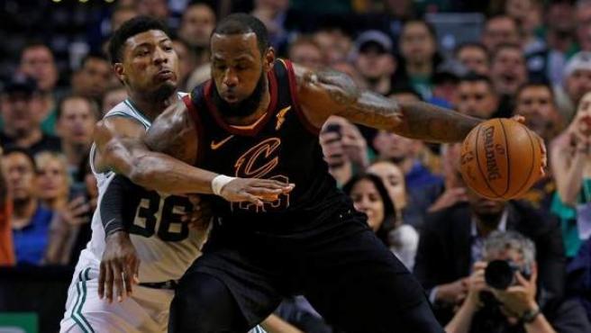 LeBron James, de los Cleveland Cavaliers, defiende el balón ante Marcus Smart, de los Boston Celtics, en el séptimo partido de las finales de la Conferencia Este de la NBA.