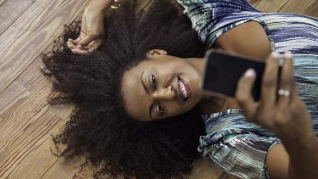 Una mujer se toma un selfie. Whatsapp usará IA para determinar si fotos como esta van a ser compartidas en la app.