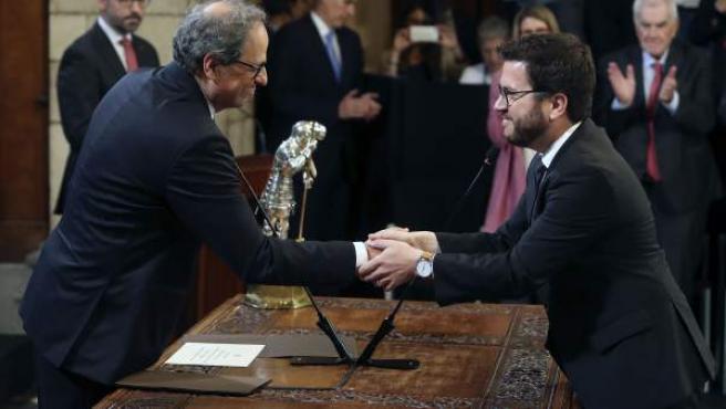 El presidente de la Generalitat, Quim Torra (i), saluda al nuevo conseller de Economia, Pere Aragonés.