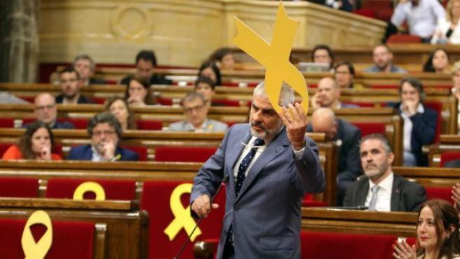 El portavoz del grupo parlamentario de Ciudadanos, Carlos Carrizosa, retira un lazo amarillo colocado en el banco del Govern, durante el pleno del Parlament.