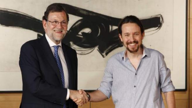 El presidente del Gobierno en funciones, Mariano Rajoy, y el secretario general de Podemos, Pablo Iglesias, se saludan antes de la reunión que han mantenido en el Congreso de los Diputados.