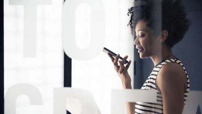 Una mujer llama por teléfono móvil.
