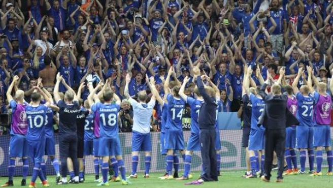 Los jugadores de la selección de Islandia celebran junto a sus aficionados la victoria ante Inglaterra en octavos de la Eurocopa.