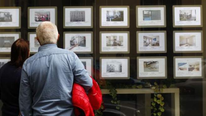 Dos personas observan la oferta inmobiliaria de una promotora.