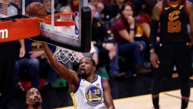 Kevin Durant, de los Golden State Warriors, entra a canasta ante JR Smith y Kevin Love, de los Cleveland Cavaliers, durante el tercer partido de las finbales de la NBA.