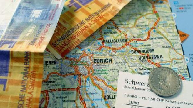 Varios billetes de francos suizos sobre un mapa del país.