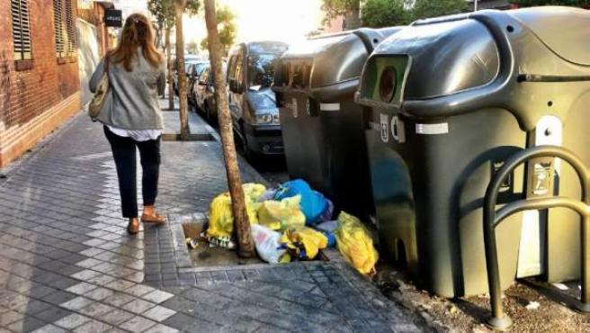 Una vecina pasa junto a los nuevos contenedores de basura.