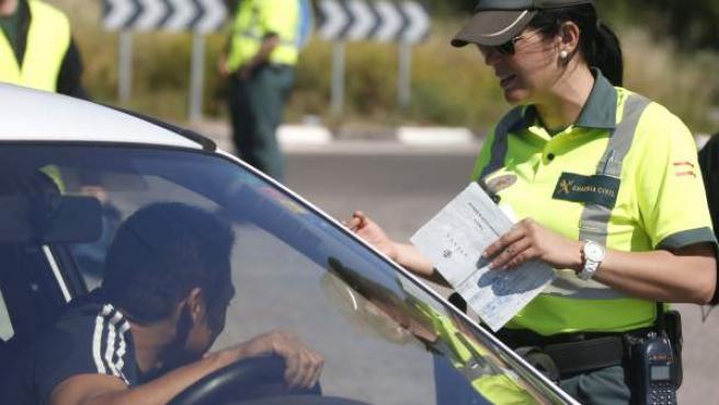 Una agente de la Guardia Civil de Tráfico pide la documentación a un conductor.