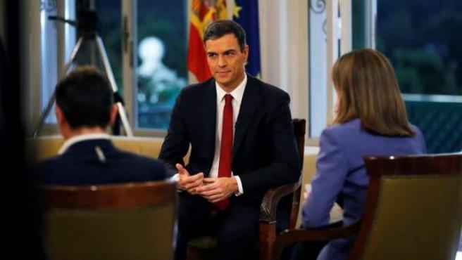 El presidente del Gobierno, Pedro Sánchez, con los presentadores Ana Blanco y Sergio Martín, de TVE, al comienzo de su primera entrevista desde que accedió al cargo, en el Palacio de La Moncloa.