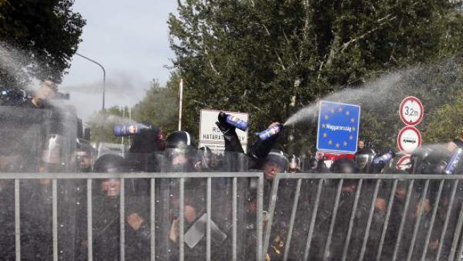 La Policía húngara usa gas pimienta y un cañón de agua contra un grupo de refugiados que trató de cruzar la frontera desde la localidad serbia de Horgos, en 2015.