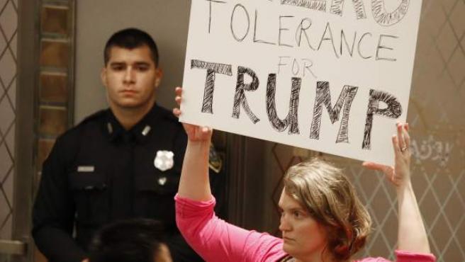 Una mujer sostiene un cartel contra Trump durante la conferencia de prensa del alcalde de Houston.