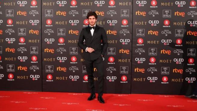 El actor Quim Gutiérrez posa, con un elegante esmoquin de Dsquared2 y una pulsera de platino de los años 20, a su llegada a la alfombra roja de los Premios Goya 2018.