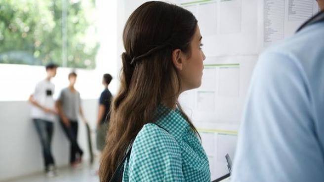 Unos adolescentes mirando el tablón de notas.