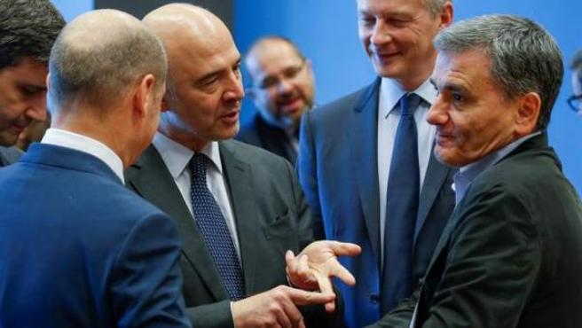 De izq. a dcha., el ministro de Finanzas alemán, Olaf Scholz; el comisario europeo de Asuntos Económicos, Pierre Moscovici; el ministro francés de Finanzas, Bruno Le Maire; y su homólogo griego, Euclid Tsakalotos, durante la reunión por el 20º aniversario del Eurogrupo, en Luxemburgo.